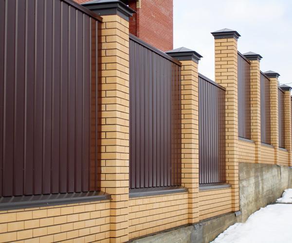 Колпаки на заборе из профнастила с кирпичными столбами
